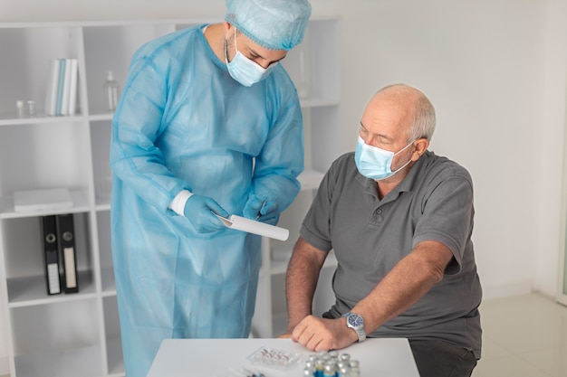 コロナウイルスの予防接種を受けている年配の男性患者