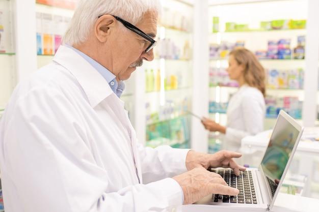 Старший фармацевт-мужчина ищет лекарство в компьютерной базе, нажимая клавиши на стойке против своего молодого коллеги на дисплее