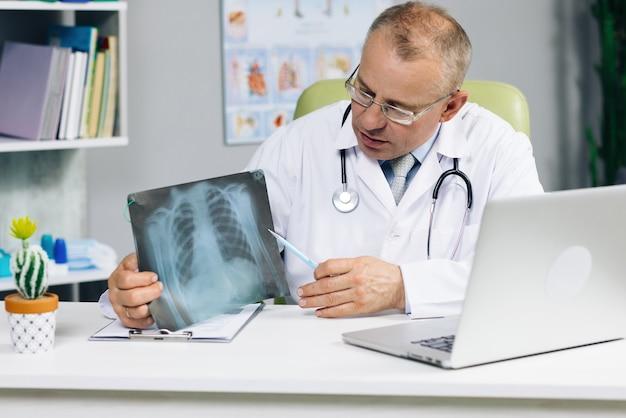 Старший врач-мужчина разговаривает, глядя на экран компьютера, общается через веб-камеру в веб-чате, консультируя клиента онлайн