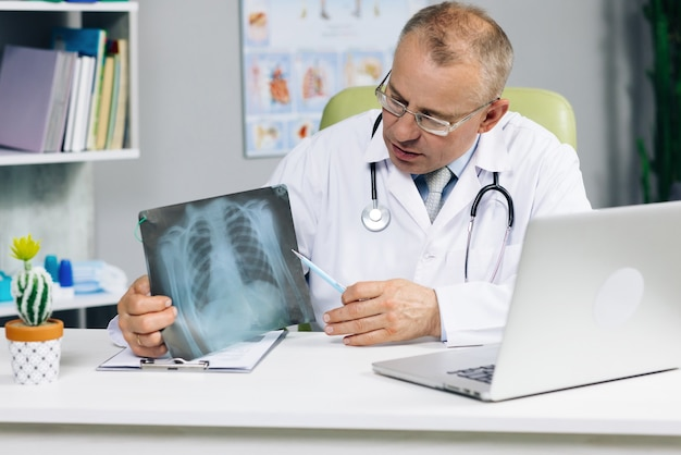 Senior male physician speaking looking at pc screen communicating by webcam in web chat consulting client online