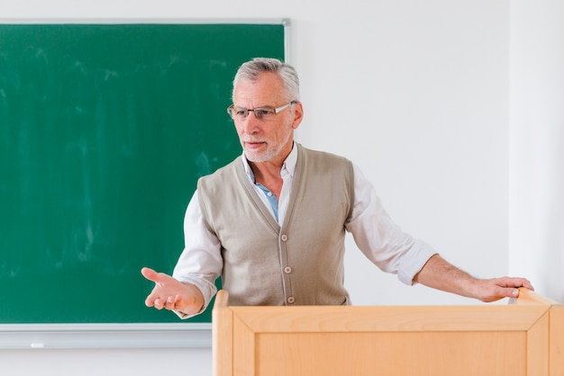 Senior male professor explaining lesson near chalkboard