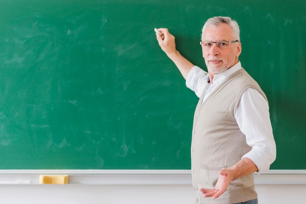 Senior male professor explaining and writing on green chalkboard
