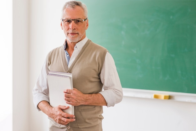 Senior male professor in glasses holding notebook standing against blackboard