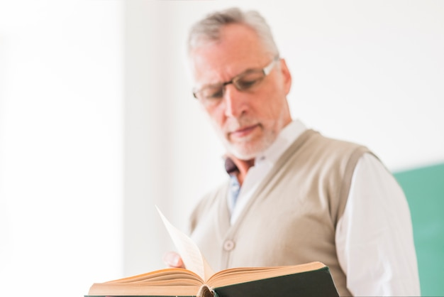 Senior male professor in glasses reading book