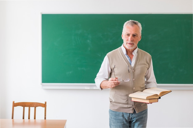 Senior male professor holding books and glasses against blackboard