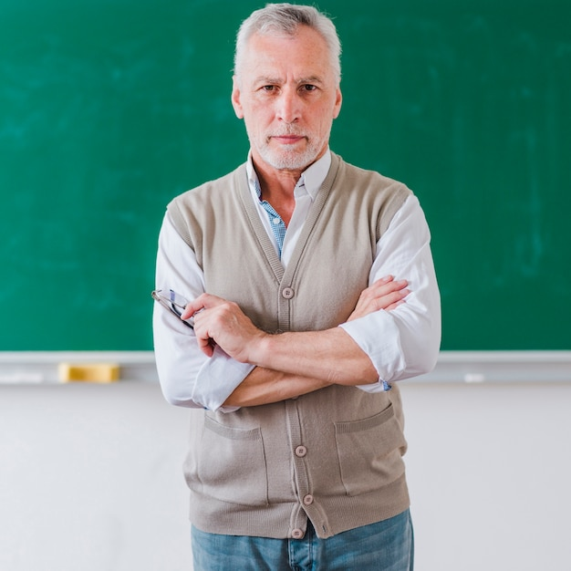 Senior male professor with arms crossed standing against chalkboard