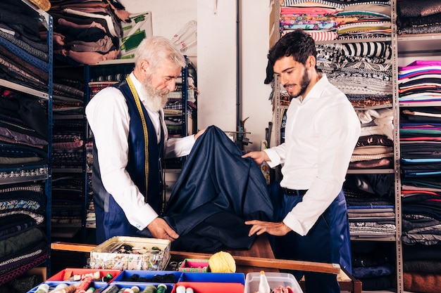 Senior male seller offering fabrics to young man in textile shop