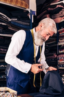 Senior male tailor cutting piece of cloth at table in his shop