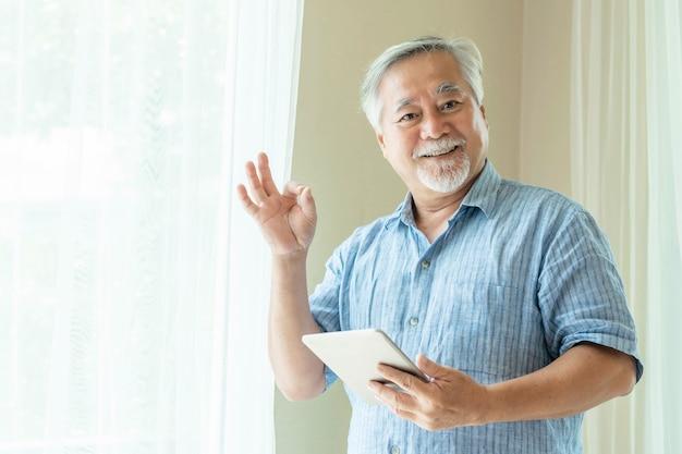 スマートフォンを使用して、手、タブレットコンピューター、笑顔でokサインを示すシニア男性が自宅の寝室で幸せを感じる-ライフスタイルシニアコンセプト
