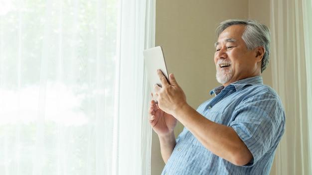 スマートフォン、タブレットコンピューター、笑顔を使用してシニア男性が自宅の寝室で幸せを感じる-ライフスタイルシニアコンセプト