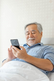 Senior male using a smartphone , smiling feel happy in bed at home - lifestyle senior concept