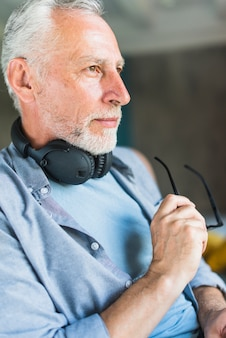 Senior male with headphone around his neck holding eyeglasses