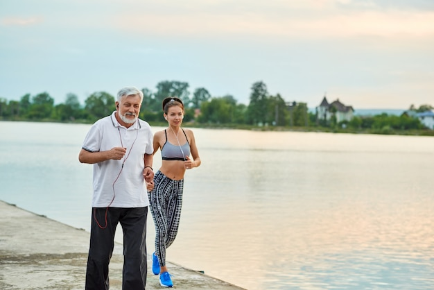 Senior man and active young girl running near city lake. active lifestyle, healthy body.