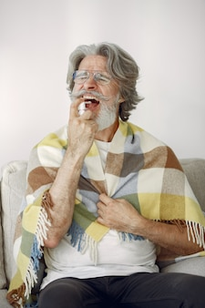 年配の男性だけでソファーに座っていた。病人は格子縞で覆われています。一杯のお茶とおじいちゃん。