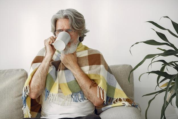 Только старший мужчина сидит на софе. больной, покрытый пледом. grangfather с чашкой чая.