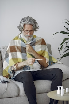 Senior man alone sitting on sofa. sick man covered with plaid. grangfather with thermometer.