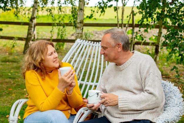 안락의자에 앉아 정원에서 차를 마시는 노인 남녀
