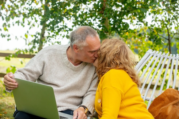 안락의자에 앉아 정원에서 노트북을 사용하는 노인 남녀