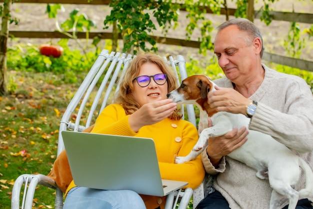 강아지와 함께 안락의자에 앉아 정원에서 노트북을 사용하는 노인 남녀