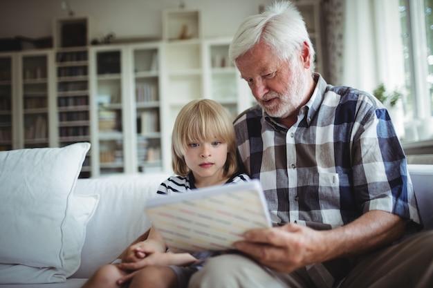Старший мужчина и ее внучка, глядя на фотоальбом