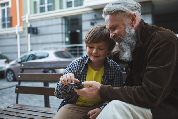 スマートフォンを一緒に使う年配の男性と孫