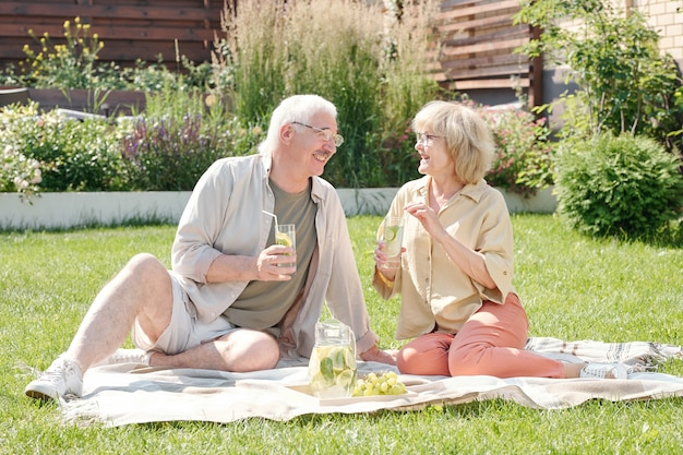 裏庭の芝生に座って新鮮なレモネードを飲みながらおしゃべりする年配の男性と彼の素敵な妻