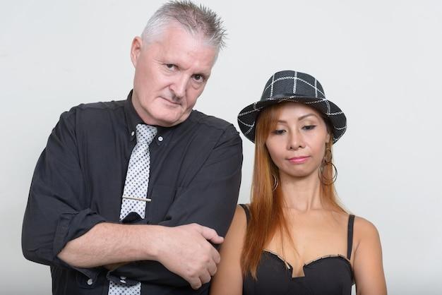 一緒にカップルとして、白人に対して恋をしている年配の男性と成熟したアジアの女性