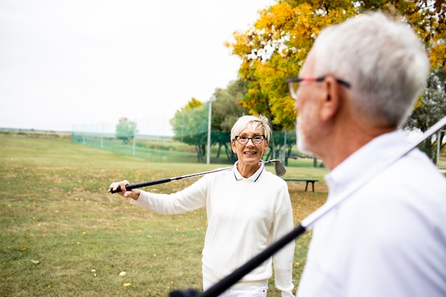 Старший мужчина и женщина собираются вместе играть в гольф и наслаждаться свободой.