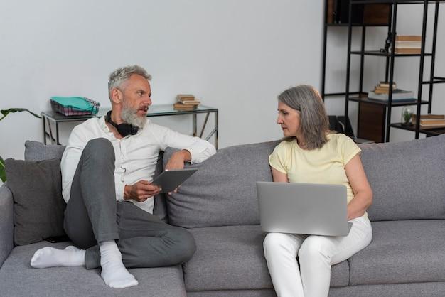 Старший мужчина и женщина дома на диване, используя ноутбук и планшет