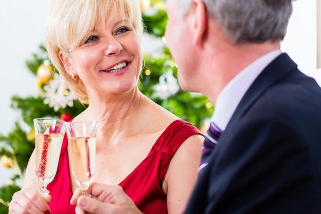 Старший мужчина и женщина празднуют канун рождества с бокалом игристого вина