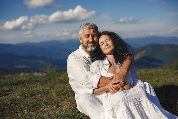 山の中の年配の男性と女性。日没で恋をしている大人のカップル。白いシャツを着た男。空の背景に座っている人。