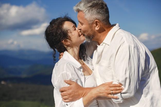 Старший мужчина и женщина в горах. взрослая влюбленная пара на закате. мужчина в белой рубашке.
