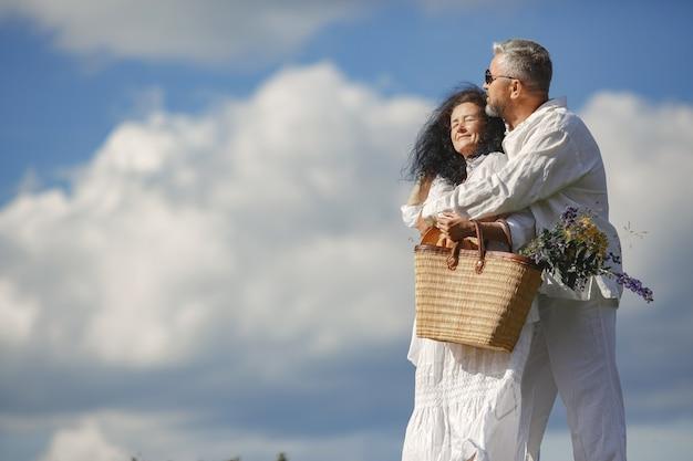Старший мужчина и женщина в горах. женщина с корзиной цветов. мужчина в белой рубашке.