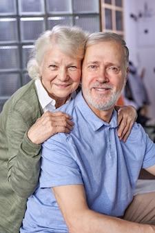 カメラの笑顔、自宅でポーズ、週末の余暇、幸せな退職を見て年配の男性と女性。肖像画