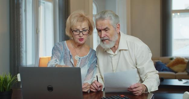 수석 남자와 여자는 청구서를 지불하고 예산을 관리합니다. 성숙한 걱정 커플 앉아서 집에서 비용을 관리.