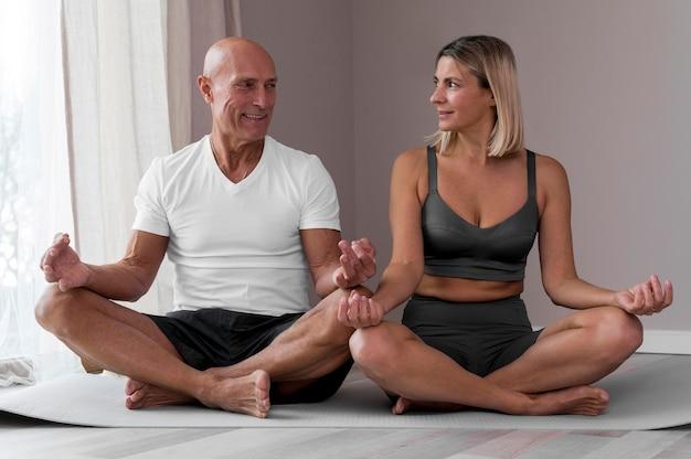 Старший мужчина и женщина, сидя в позе йоги