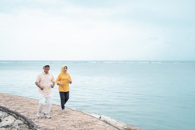 年配の男性と女性が一緒にビーチを走る