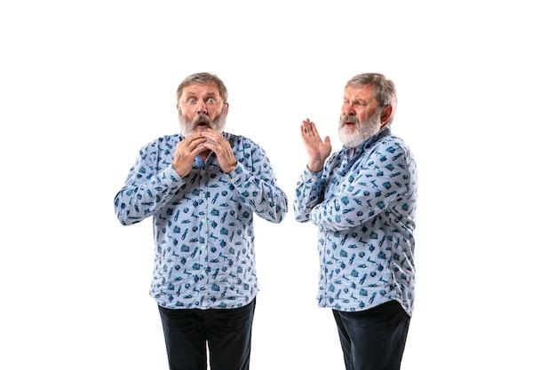 Старший мужчина спорит с собой на фоне белой студии.