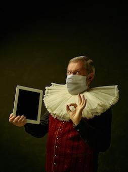 코로나바이러스에 대한 보호 마스크를 쓰고 어두운 배경에 중세 기사로 수석 남자