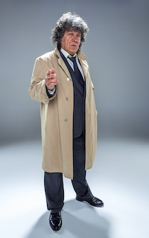 The senior man as detective or boss of mafia on gray studio background