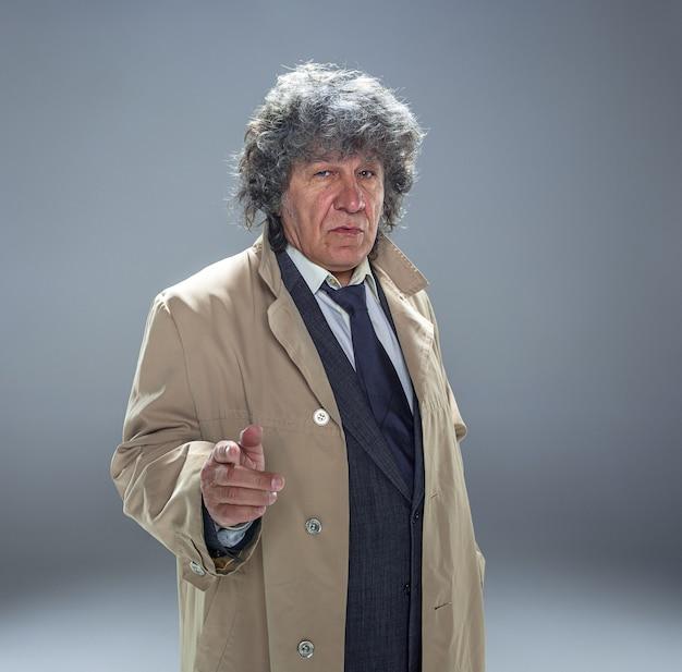 The senior man as detective or boss of mafia on gray studio