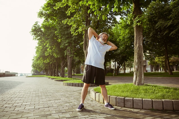 街の通りのランナーとしての年配の男性。夏の朝の白人男性モデルのジョギングと有酸素運動。牧草地の近くでストレッチ体操をしています。健康的なライフスタイル、スポーツ、活動の概念。
