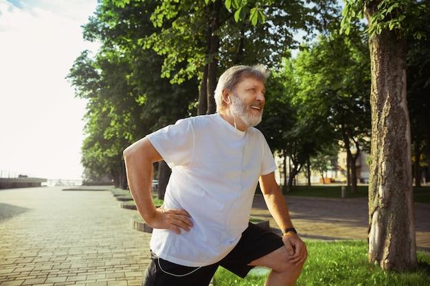 Старший бегун на городской улице. кавказская мужская модель бег трусцой и кардио-тренировка в летнее утро. делаем упражнения на растяжку возле луга. здоровый образ жизни, спорт, концепция деятельности.