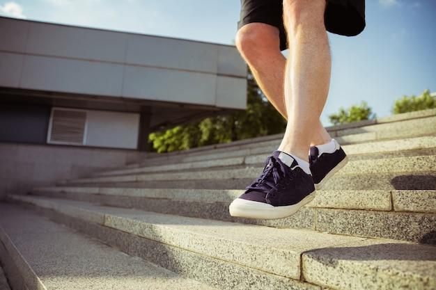街の通りのランナーとしての年配の男性。スニーカーの足のクローズアップ。夏の朝の白人男性モデルのジョギングとカーディオトレーニング。健康的なライフスタイル、スポーツ、活動の概念。