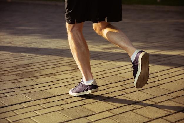 街の通りのランナーとしての年配の男性。スニーカーの足のクローズアップショット。夏の朝の白人男性モデルのジョギングと有酸素運動。健康的なライフスタイル、スポーツ、活動の概念。