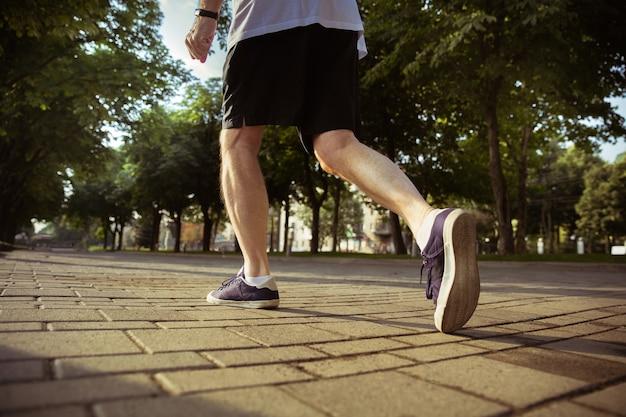 도시의 거리에서 주자로 수석 남자. 운동화에 다리의 총을 닫습니다. 백인 남성 모델 조깅과 여름 아침에 심장 훈련. 건강한 라이프 스타일, 스포츠, 활동 개념.