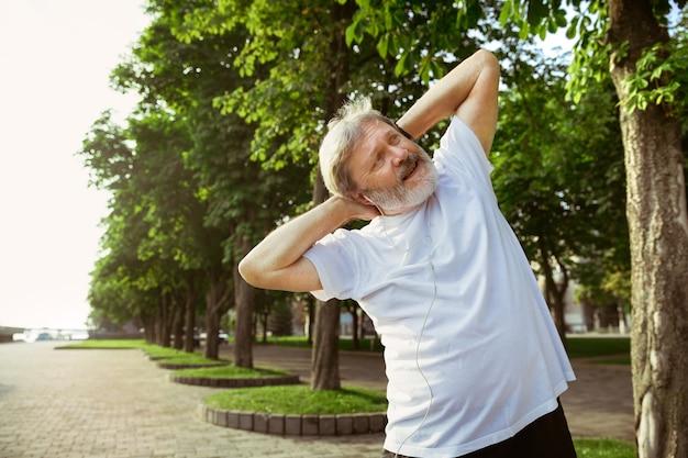 Uomo anziano come corridore in strada della città. modello maschio caucasico fare jogging e allenamento cardio nella mattina d'estate. fare esercizi di stretching vicino al prato. stile di vita sano, sport, concetto di attività.