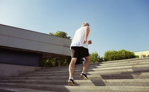 Uomo anziano come corridore con fascia da braccio o fitness tracker in strada della città. modello maschio caucasico che pratica corsi di jogging e cardio nella mattina d'estate. stile di vita sano, sport, concetto di attività.