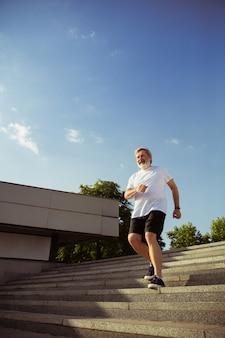 Uomo anziano come corridore con fascia da braccio o fitness tracker per la strada della città. modello maschio caucasico che pratica corsi di jogging e cardio nella mattina d'estate. stile di vita sano, sport, concetto di attività.