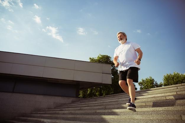 Uomo anziano come corridore con bracciale o fitness tracker in strada della città